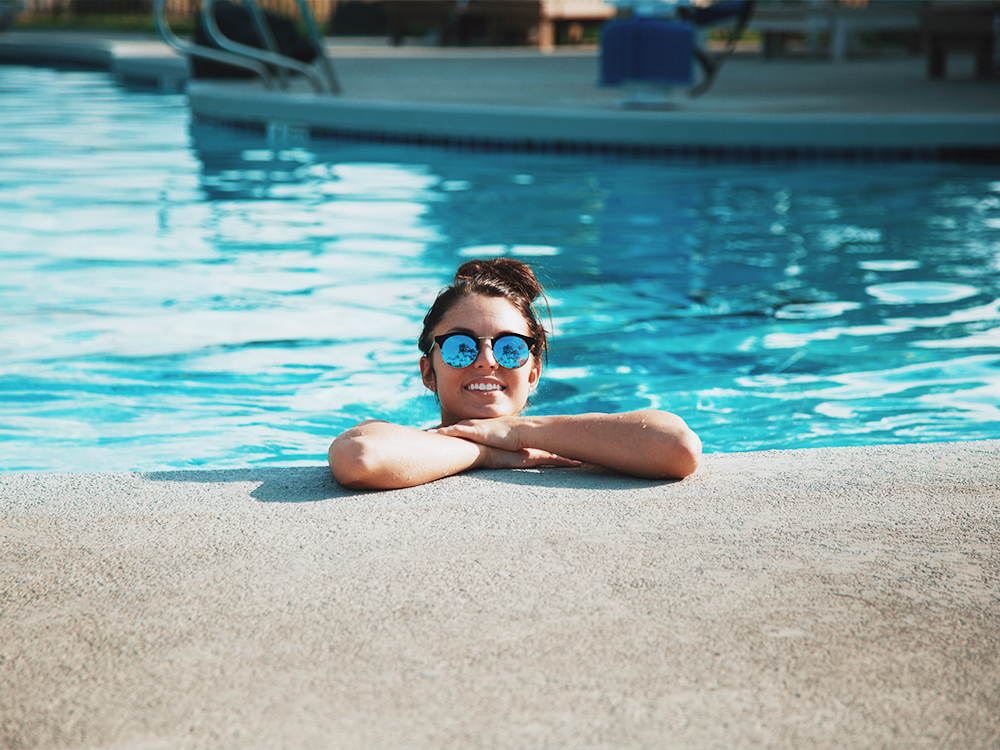 A girl with dark hair wearing reflective sunglasses at the Petrosa clubhouse outdoor pool